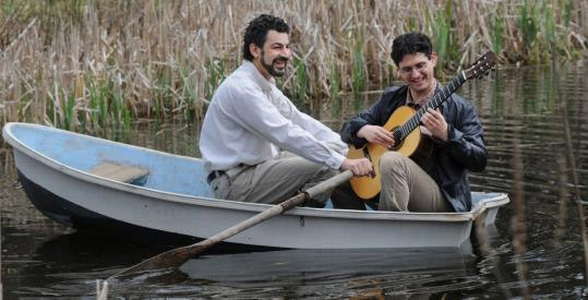Composer Jonathan Feist gives guitarist Aaron Larget-Caplan a tour of a small pond on Feist's property in Harvard. (Christine Peterson for The Boston Globe)