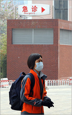 A Chinese woman arrived at a hospital wearing a surgical mask in Beijing. China rejected foreign media reports pointing to the country as the source of a deadly swine flu outbreak, saying they were baseless and aimed at tarnishing the nation's image.