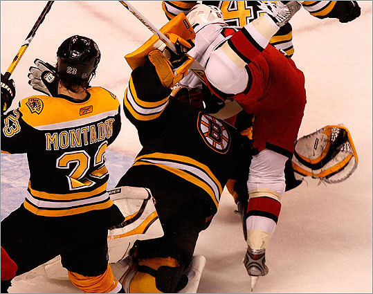 Hurricanes left wing Ryan Bayda crashed into Boston goalie Tim Thomas.
