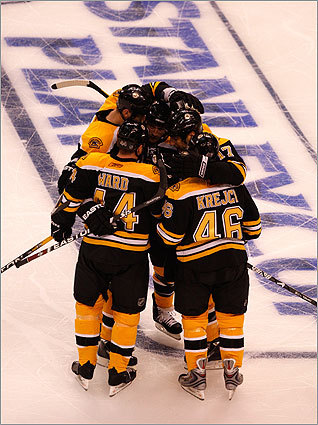The Bruins' David Krejci (46), is congratulated by teammates after his goal against the Carolina Hurricanes in Game 1 of the Eastern Conference semifinals at the TD Banknorth Garden.