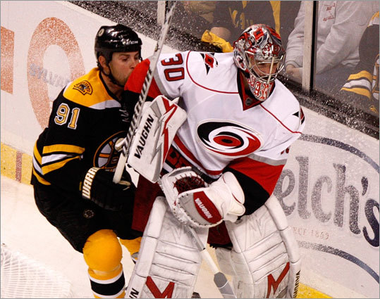 Carolina Hurricanes goalie Cam Ward (30) clears the puck from behind the net before Boston Bruins center Marc Savard (91) can get there.