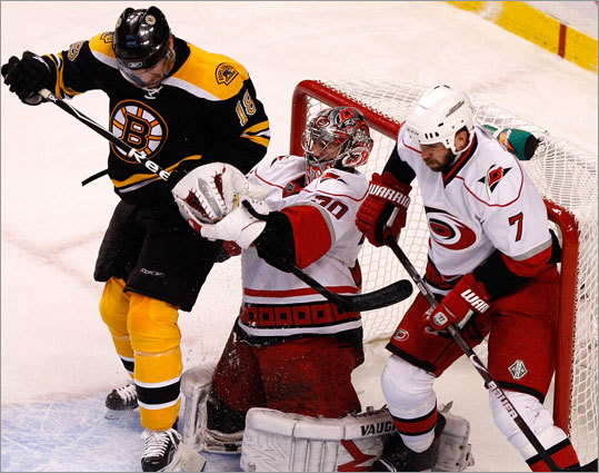 Carolina Hurricanes goalie Cam Ward (30) makes a first-period save in front of Boston's Stephane Yelle (18).