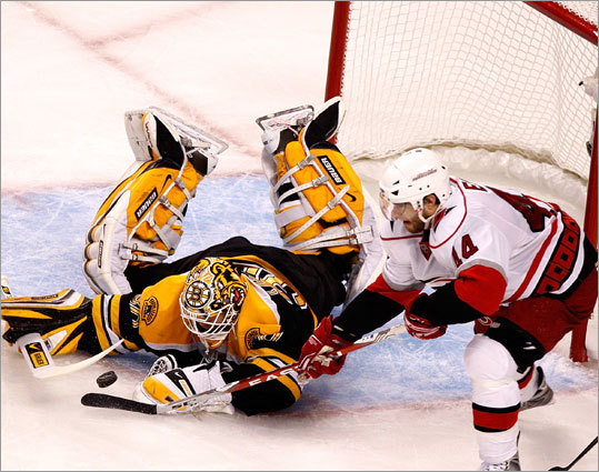 Bruins goalie Tim Thomas (30) sprawls to cover up the puck near Hurricanes left wing Sergei Samsonov (14).