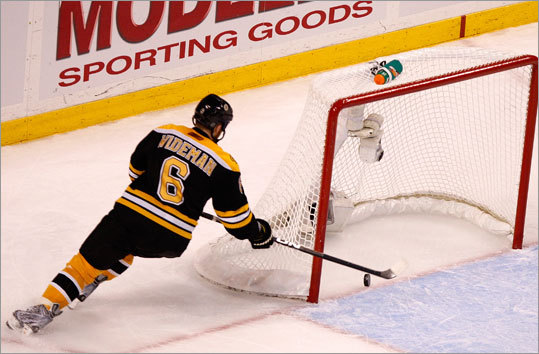 Bruins defenseman Dennis Wideman fishes the puck out of the net after Eric Staal scored an empty netter late in the third period.