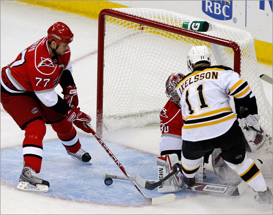 Carolina Hurricanes goalie Cam Ward (30) gets his stick on a shot by Bruins left wing P.J. Axelsson (11).