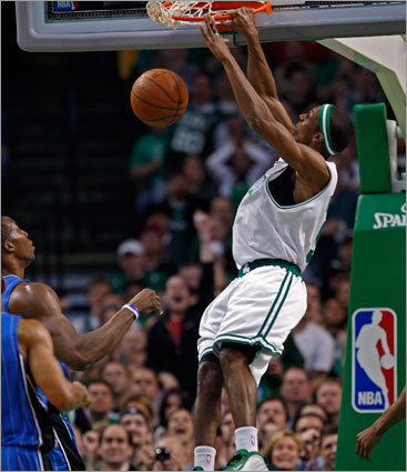 The Celtics Rajon Rondo sails over the Magic's Dwight Howard for an emphatic jam near the start of the third quarter.