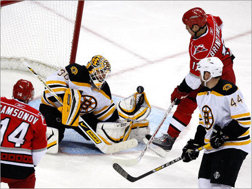 Goalie Tim Thomas (30) got a piece of the puck with his glove, but it was knocked free to score one of three third period goals by the Carolina Hurricanes.