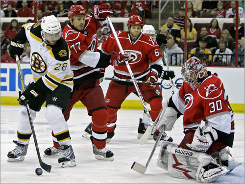 Bruins winger Mark Recchi (28) looked to shoot as Joe Corvo (77) Tim Gleason (6) and goalie Cam Ward (30) of the Hurricanes looked on.