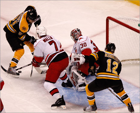 Bruins right wing Phil Kessel (left) tried to get a shot off against Hurricanes goalie Cam Ward (30) in the first period.