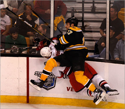 Bruins left wing Milan Lucic (17) drove Canes defenseman Dennis Seidenberg (4) into the boards in the first period.