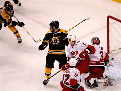 Bruins right wing Phil Kessel (left) snapped Boston's second goal past Canes goalie Cam Ward (right) in the first period.