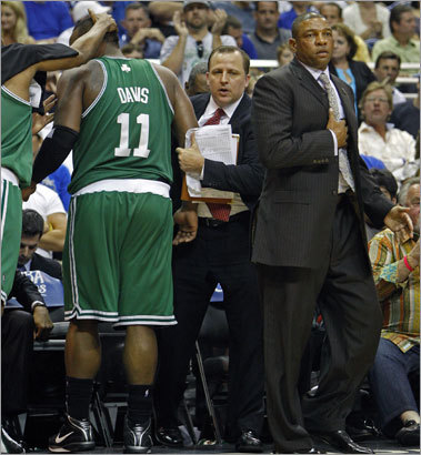 Celtics head coach Doc Rivers feigns heart palpitations after avoiding a collision with Davis, who charged towards the bench chasing a loose ball.