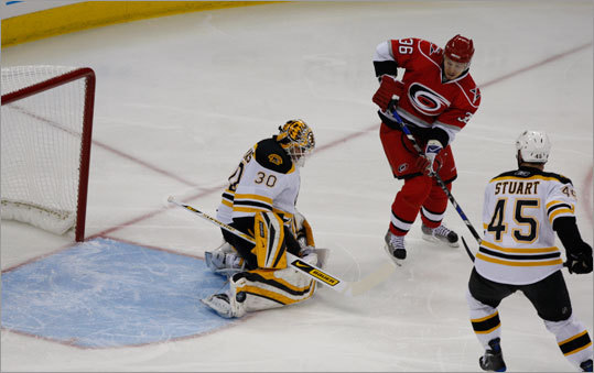 Bruins netminder Tim Thomas (30) makes a stop on Carolina's Jussi Jokinen (36) as Mark Stuart (45) patrols nearby.