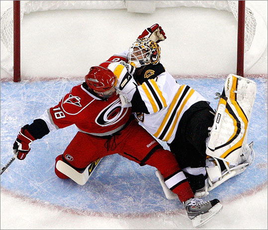 Carolina's Ryan Bayda (18) collides with Bruins goalie Tim Thomas (30) in the goalie crease.