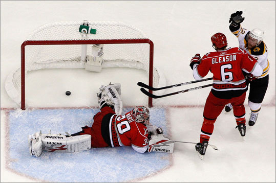 Bruins right wing Chuck Kobasew (12) scores in the second period as Hurricanes goalie Cam Ward (30) lays on the ice.