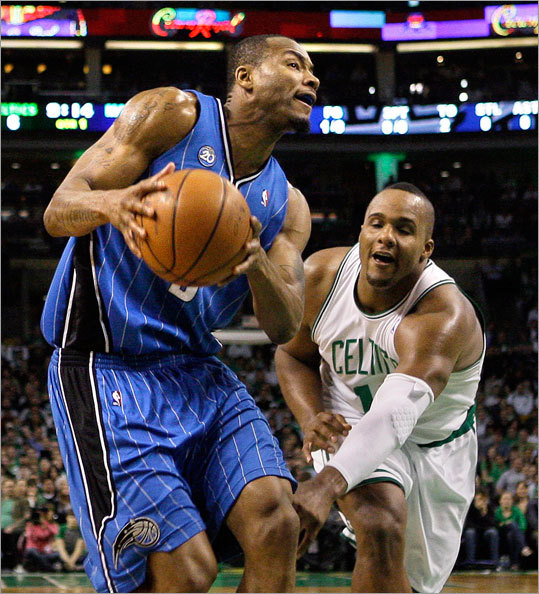 Boston's Glen Davis, right, reaches in to defend against Orlando's Rashard Lewis.