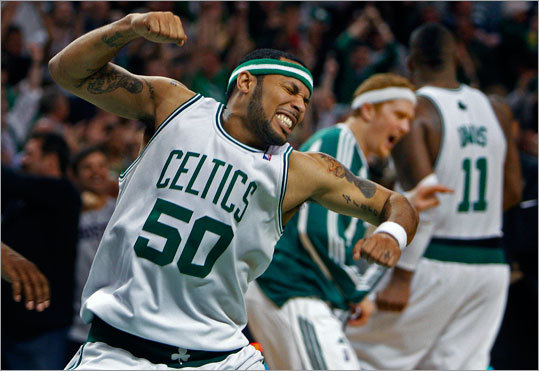 Eddie House celebrates following Boston's victory as Brian Scalabrine (background) congratulates Glen 'Big Baby' Davis near the bench.