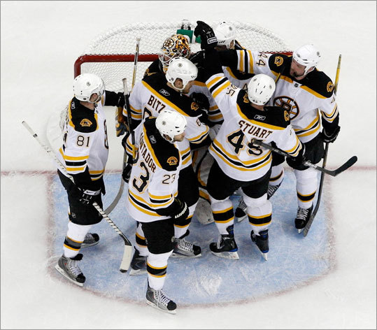 The Bruins celebrate around goaltender Tim Thomas after defeating the Hurricanes in Game 6 in Raleigh.