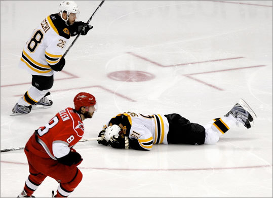 Bruins center Marc Savard (91) lays on the ice after taking a hit to his knee in the third period.