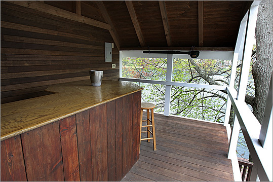 Outside is a large poured-concrete deck with mahogany railings, a gazebo with a bar and stairway to private dock.