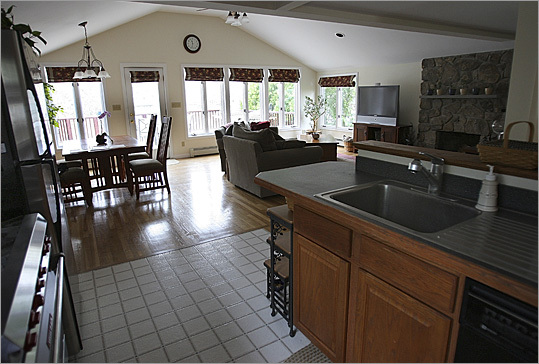 First is the gourmet oak kitchen with lots of cabinets and pantry space, a large Vulcan six-burner stove, and a pot hanger above the sink.