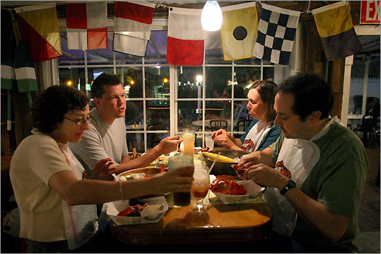 Lynn and Mark Krueger (left) and Erica and Barry Crell dig into lobsters at Shuckers, a traditional seafood restaurant in the center of Woods Hole.