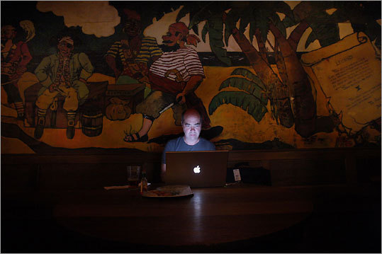Summer resident Paul Cormack of Toronto works on his laptop at The Captain Kidd Bar in Woods Hole.