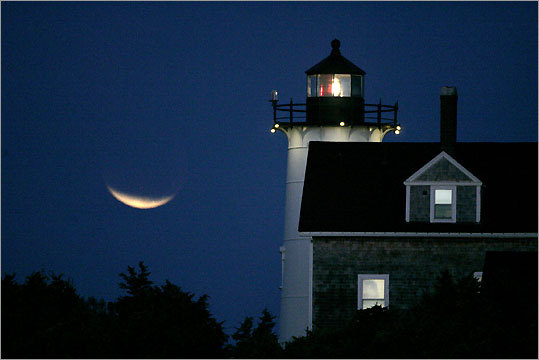 In Woods Hole, Nobska Point Light shines against a lunar eclipse.