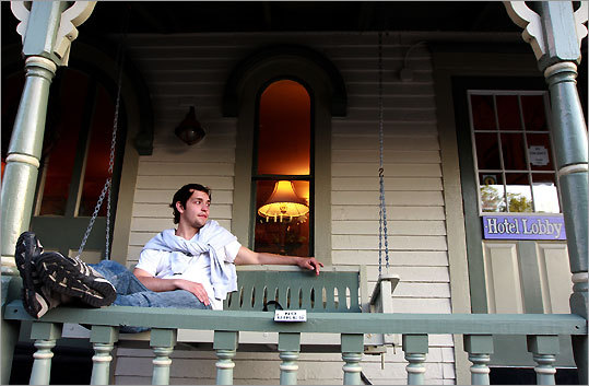 Alexander Fadachen from the Ukraine rests in a swinging chair on the porch of The Nashua House Hotel on Kennebec Avenue in Oak Bluffs.
