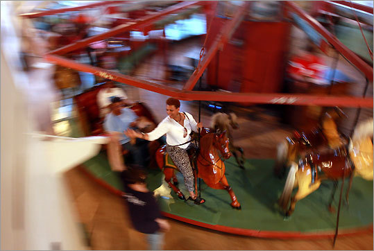 Riders grab rings from a post in Flying Horses Carousel in Oak Bluffs. Riders who grab a brass ring get an additional free ride. The nation's oldest platfrom carousel is still just $1.50 a ride; fun for all ages.