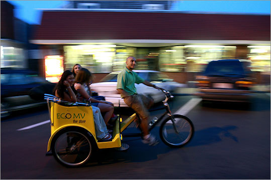A pedicab transports sightseers down Circuit Ave. in Oak Bluffs.