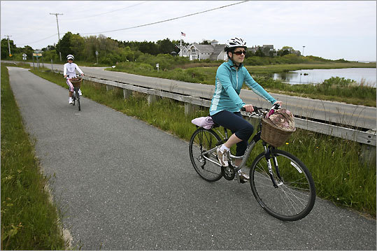 Adrienne Craig (right) and Dale LeFebvre ride along the bike path past the Ship Wreck and Lifesaving Museum on Nantucket Island.