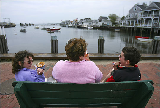 Judy Harrington sits with her niece Rian Reppert, 8, (left) and nephew Ben Reppert, 11 (right), while eating ice cream and enjoying a view of the Easy Street Boat Basin on Nantucket Island.