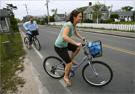 Emma Sopko (right) and her husband Jeff Sopko from Virginia ride their rental bikes down Washington Street on Nantucket Island.