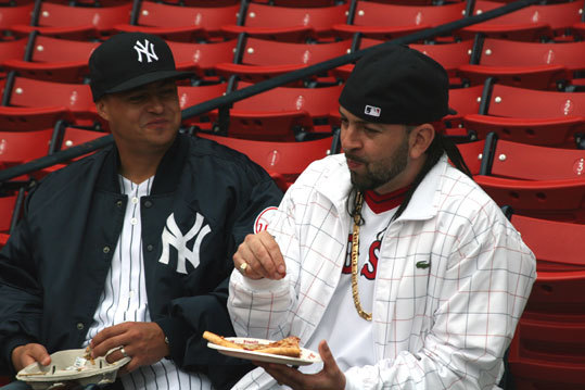 Yankees fan Michael Brown, from Medford, and his brother, Red Sox fan Mark Girardin, from Cambridge, enjoy some pizza before the first pitch.