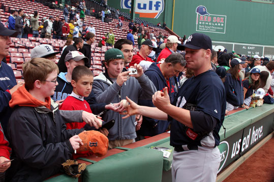 Yankees lefthander Phil Coke signs autographs for fans before the start of Tuesday night's game.
