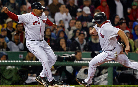 Red Sox third base coach DeMarlo Hale waves Kevin Youkilis home in the fourth inning.