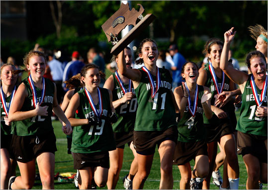 Members of the Westwood girls' lacrosse team celebrate with the Division 1 state championship trophy after rallying for an 11-10 triumph over Longmeadow. Stroll through our gallery for more photos from this contest, and Walpole's victory over St. John's (Shrewsbury) in the Division 2 boys' title game.