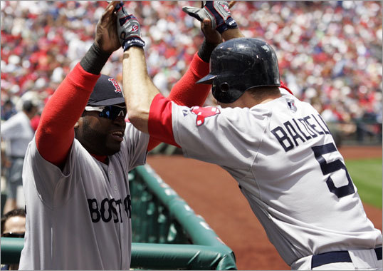 David Ortiz (left), who was not playing Sunday, greeted Rocco Baldelli after his solo home run in the second inning.