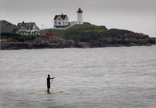 "Don McDowell of Kittery Point, Maine, surfs between Long Sands Beach and Nubble Light. Cape Neddick Light Station, or ""Nubble Light,"" is among the most photographed beacons in Maine."