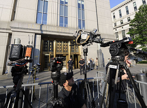 Media gather in the front of the courthouse.