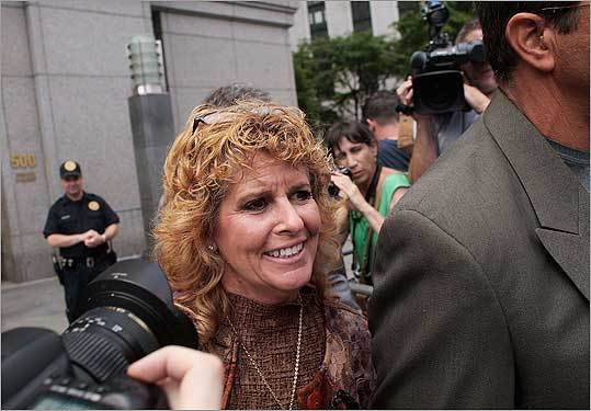 A victim of disgraced financier Bernard Madoff's Ponzi scheme smiles as she exits a Manhattan courthouse after Madoff was sentenced to 150 years in prison in New York City. The judge in the case handed down the maximum allowable sentence to Madoff in a courthouse packed with his victims who gave statements about how he affected their lives.