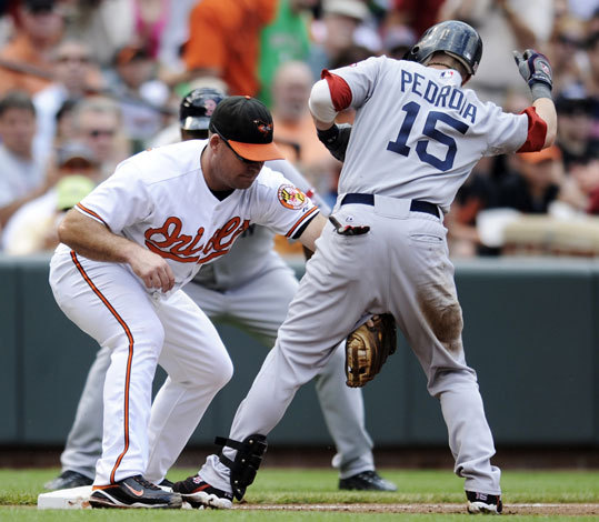 Baltimore Orioles third baseman Ty Wigginton, tags out Red Sox second baseman Dustin Pedroia as he tried to stretch a double during the third inning.