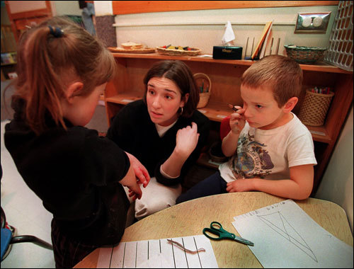 Sarah Colman kneels to make eye contact as she helps Ashley Medeiros at the Tufts day-care center.