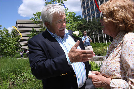 Here, Chiofaro talks with Jackie Campos with his harbor garage in the background. He has tried using unusual tactics to call attention to his plan to tear down the Harbor Garage on Atlantic Avenue and replace it with a towering glass complex that would open a new passageway to Boston Harbor. His original plan, which called for two towers - 40 and 59 stories tall - to be connected by a terra cotta 'skyframe' was ruled too tall to meet zoning regulations .