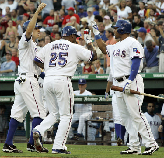 Rangers' Marlon Byrd (right) congratulates Ian Kinsler and Andruw Jones after the two scored on Hank Blalock's single in the first inning.