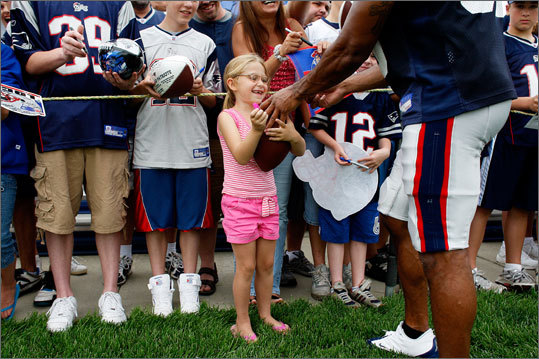 Brandon Meriweather sneaks away from drills to sign the football of Ashlee Wilson of Worcester during training camp yesterday.