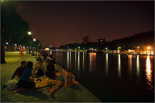 Picknickers relax on the Quai de Loire along the Bassin de la Villette