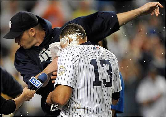 Yankees pitcher A. J. Burnett (left) stuffed a towel filled with shaving cream in Rodriguez's face as the Yankees celebrate the victory.