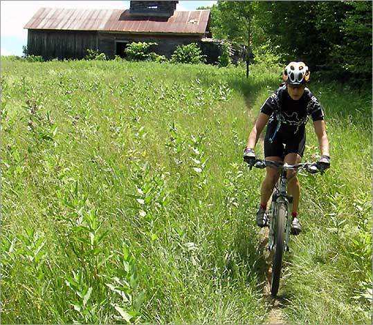 Speed is one of the Kingdom Trails thrills for bikers pedaling past the old sugarhouses on Darling Hill in East Burke.